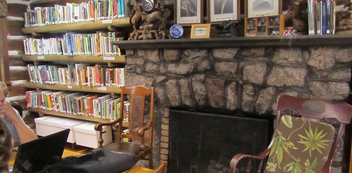 The cozy stone fireplace reading area of The Forest Lodge Library in Cable, Wisconsin.